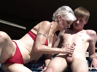 Kinky granny in thongs sucks a big hard penis be proper of three young guy